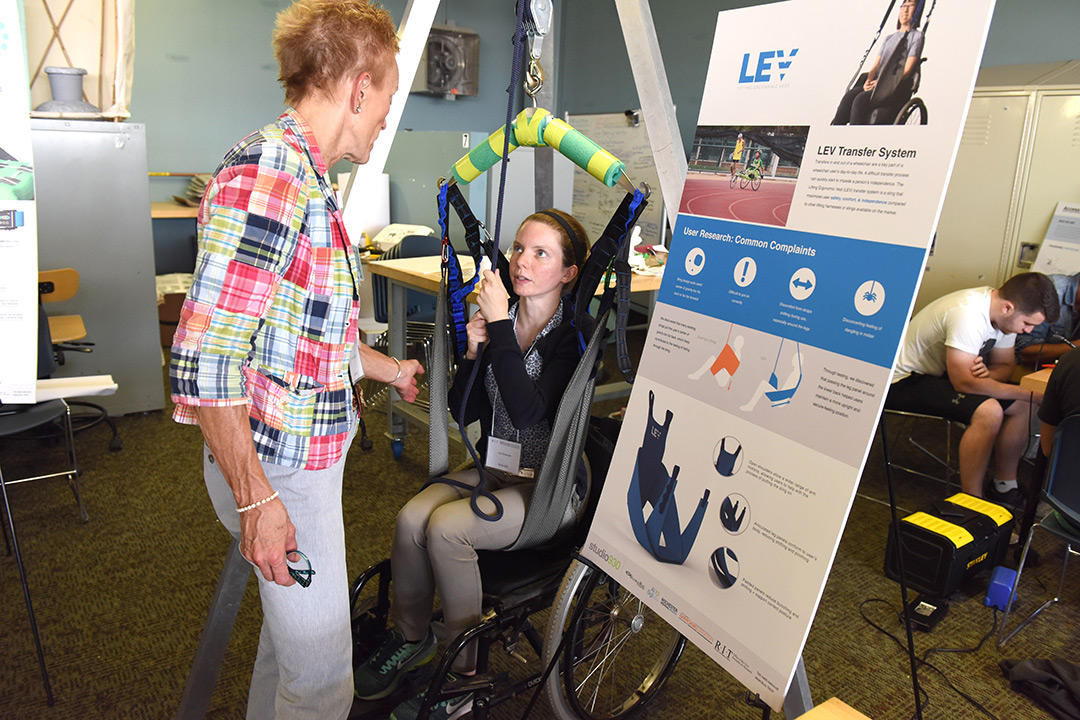 Ana Sorensen sits in a wheelchair and demonstrates how the LEV lift works for individuals to lift themselves up. She shows this to another woman who is engaged in the demonstration and reaches out to touch the assistive device.