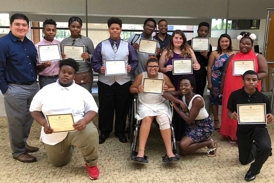 The students who participated in RIT Upward Bound Classic summer program hold up their certificates for completing the program.