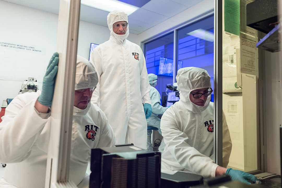 Three researchers dressed in white, sterile jumpsuits work together in a lab.