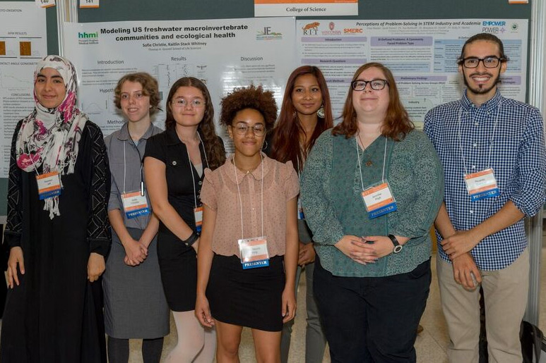 The Inclusive Excellence researchers pose for a photo together in front of their research posters.