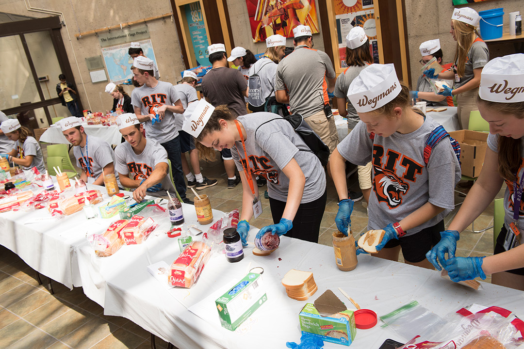 Students form an assembly line making peanut butter and jelly sandwiches. All of them are wearing matching RIT shirts and paper Wegmans hats.
