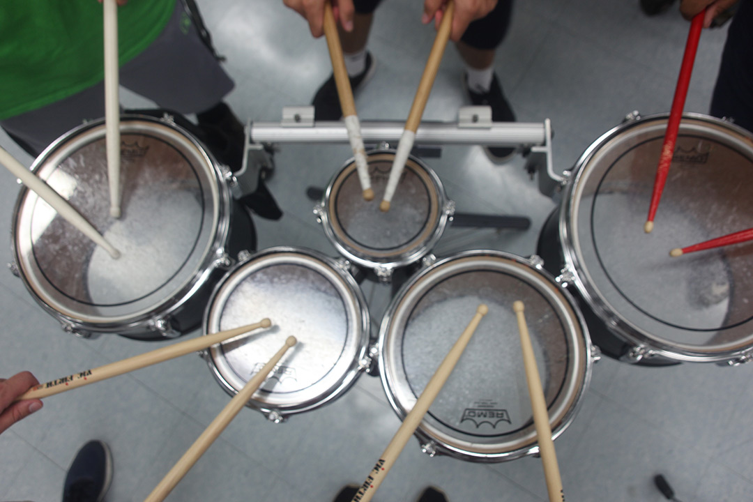 A photo looking down on a drum set with five people holding out their drum sticks over the drums, as if they are about to all play the drums at once.