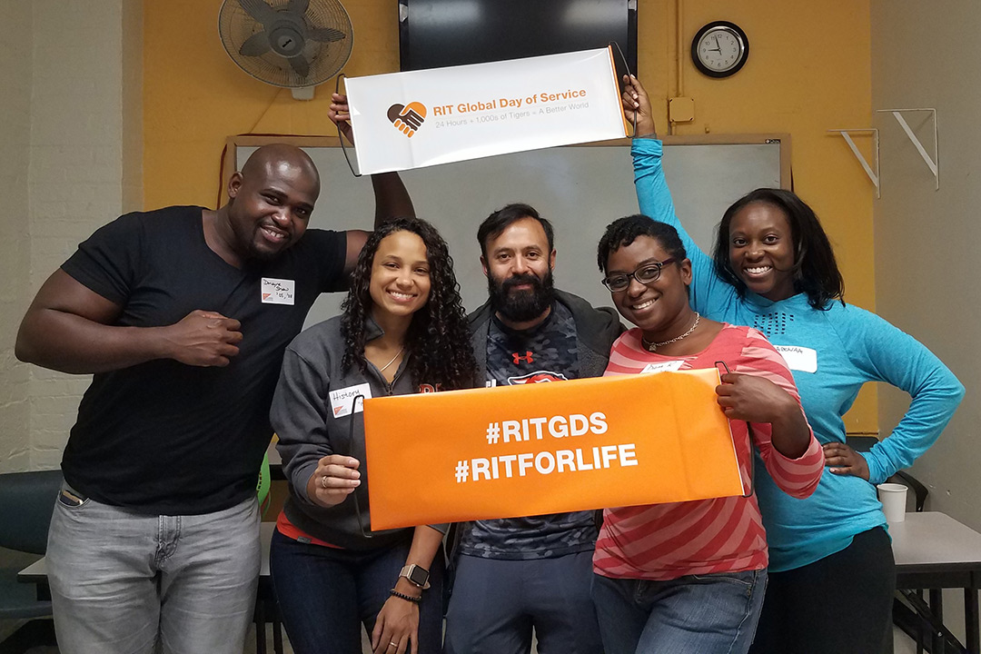"""A group of alumni pose for a photo holding two signs, one reading """"#RITGDS #RITFORLIFE"""" and the other reading """"RIT Global Day of Service."""""""