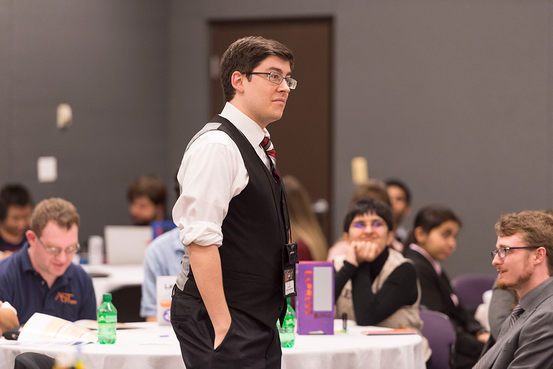 Male student with glasses dressed in suit.