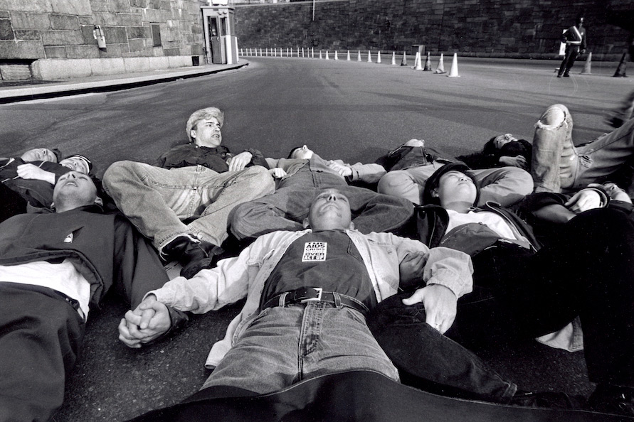 A photo taken from the exhibition which features a group of men and women laying down in the street with their arms and legs locked together in protest.
