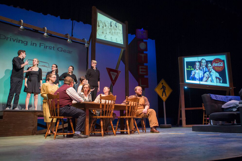 """An action photo of the cast performing the show """"How I learned to Drive."""" Six people sit and stand around a dinner table while five others dressed in black stand on a raised platform behind them."""