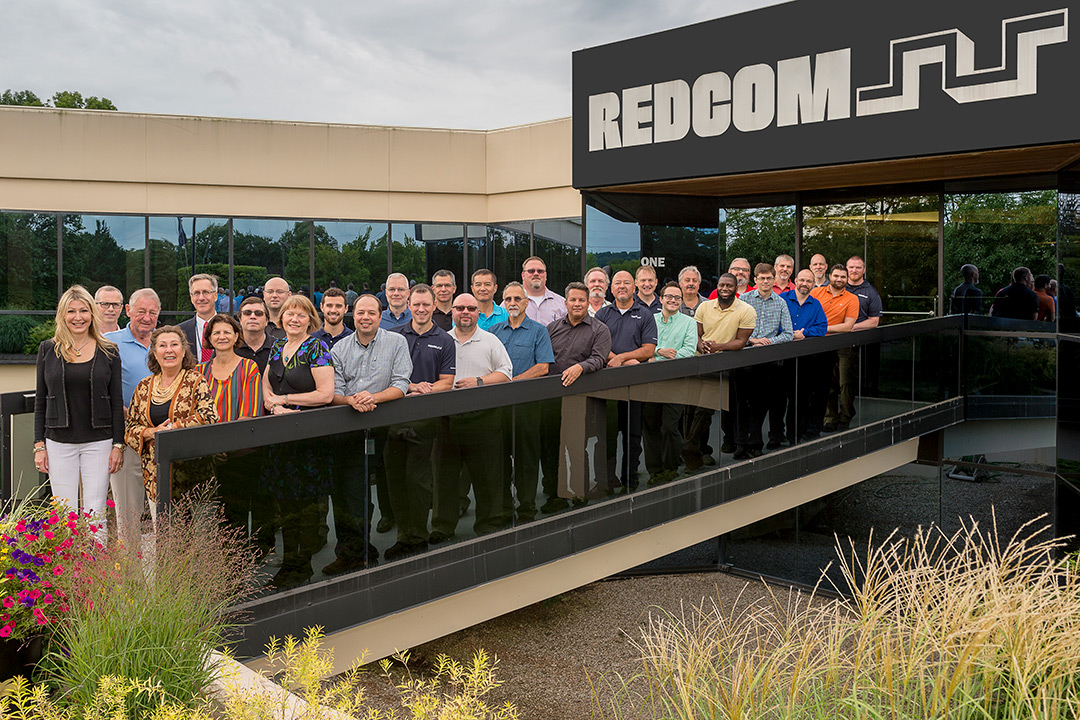 A group of people gathered on a short foot-bridge leading into REDCOM Laboratories.