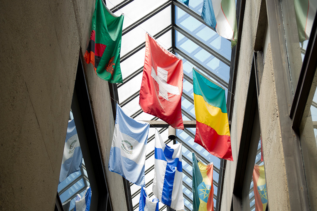 This photo looks up toward the international flags hanging in the Student Alumni Building.