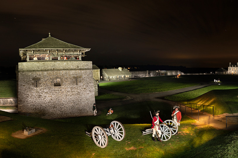 Old Fort Niagara tower with canons and actors dressed in historic clothing in foreground, image taken at night