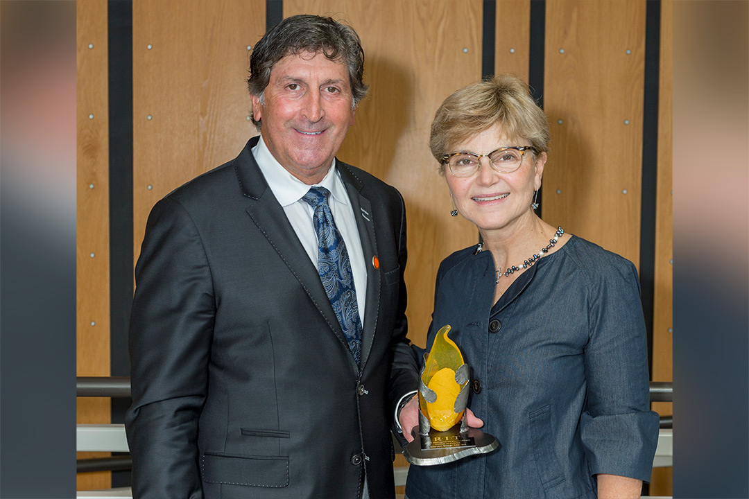 Steve Wear and Sophia Maggelakis pose for a photo together, Wear holding the distinguished alumni award trophy.