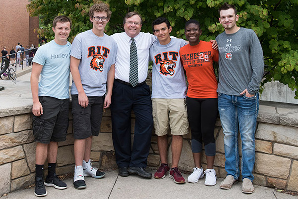 The five Magquire Scholars stand for a photo outside with RIT/NTID President Gerry Buckley.
