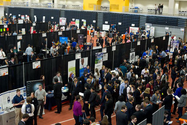 An aerial view of a crowd of students waiting in lines and interacting with potential employers at the career fair.