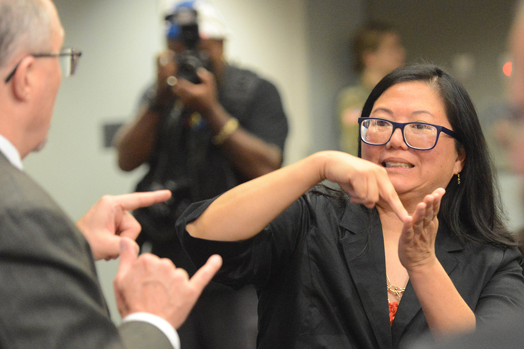 Tracy Tao-Moore communicates with another person using American Sign Language.