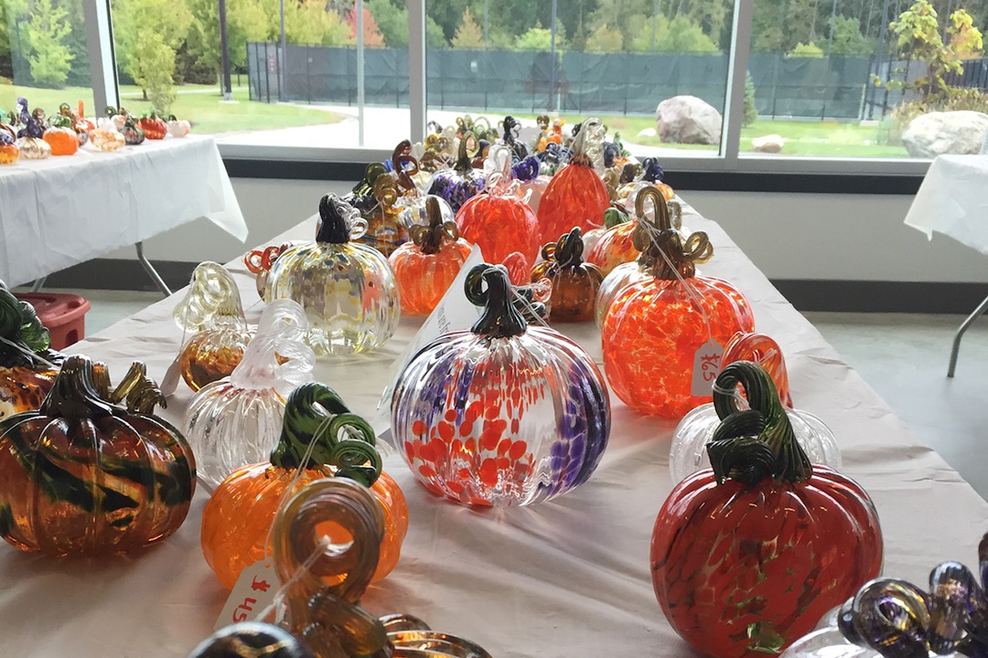 Various styles and colors of class pumpkins laid out on a white tablecloth.