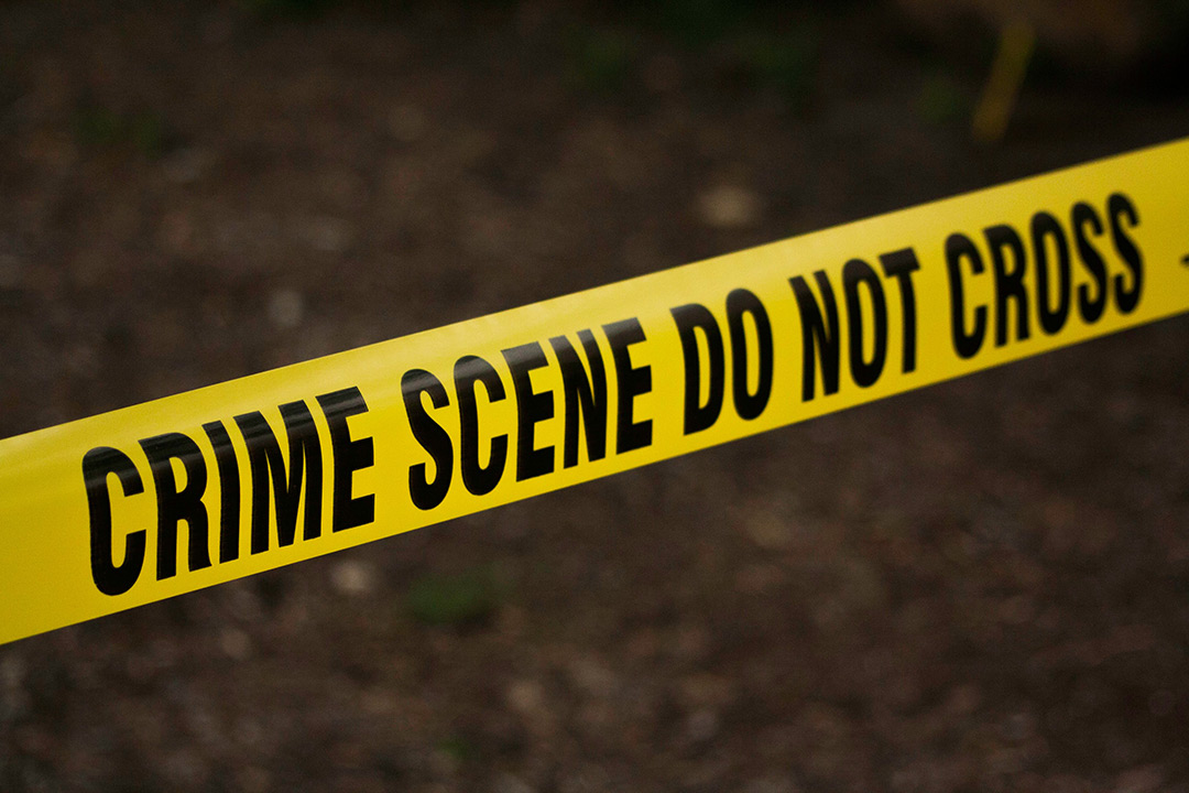 """Yellow """"Crime Scene Do Not Cross"""" police tape stretching across black pavement."""