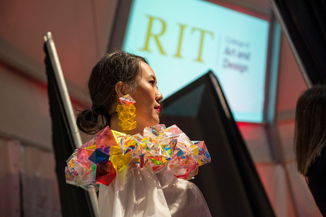 A model dressed in a white dress and colorful, 3D geometric collar and matching 3D geometric earrings.