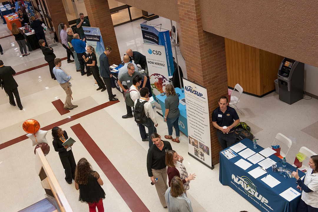 An aerial view of students interacting with employer booths at the career fair.