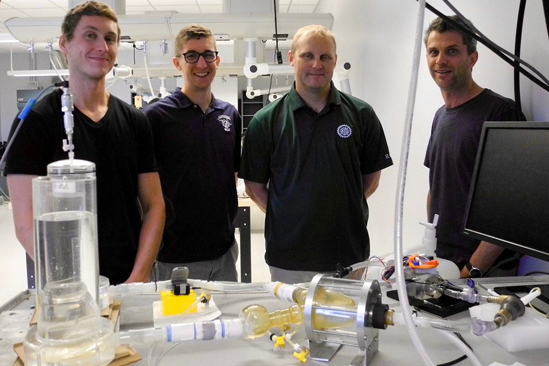Two students and two faculty members working on this project pose for a photo in front of their lab bench, which is covered in different tools and models.