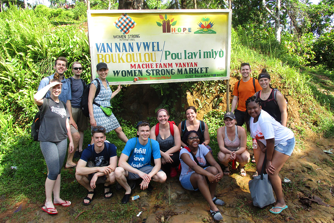"A group of students standing in front of a ""Women Strong Market"" sign. Most of the  words on the sign are in Haitian."