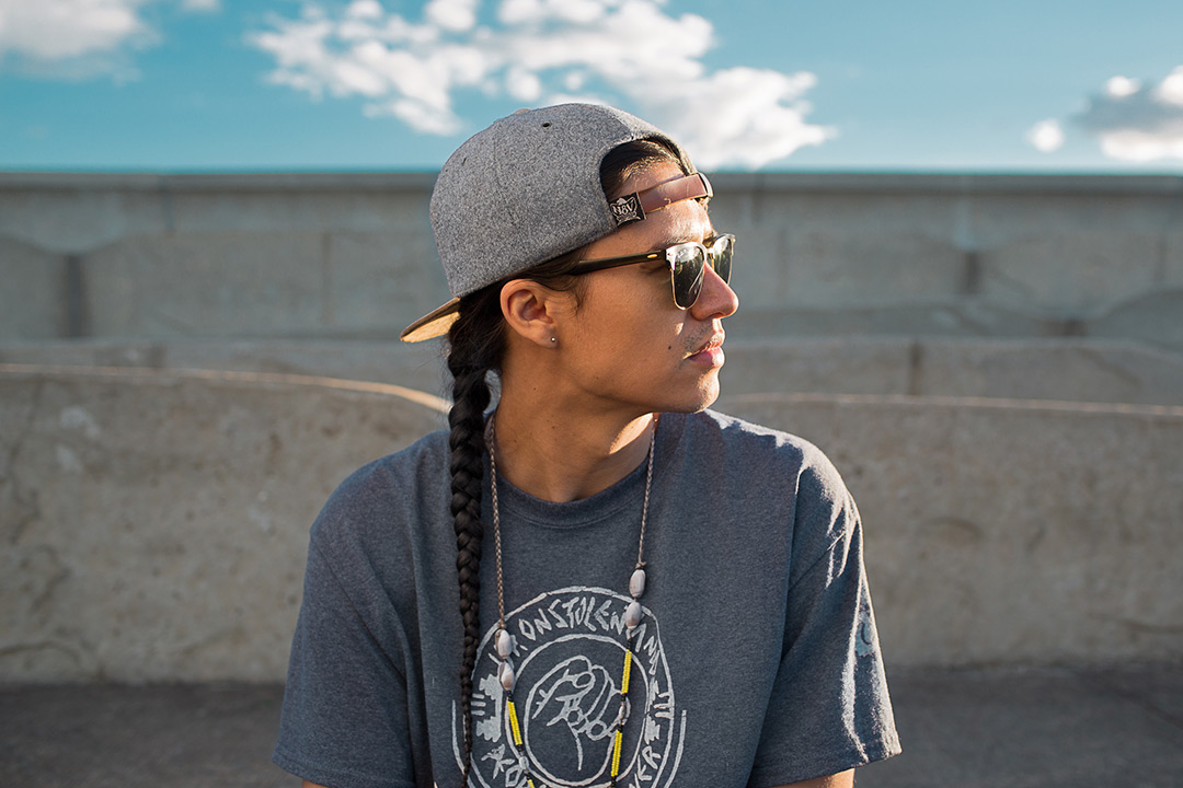 A side profile of Frank Waln looking off camera to the right. He is wearing a backward gray and brown baseball hat and a gray teeshirt.