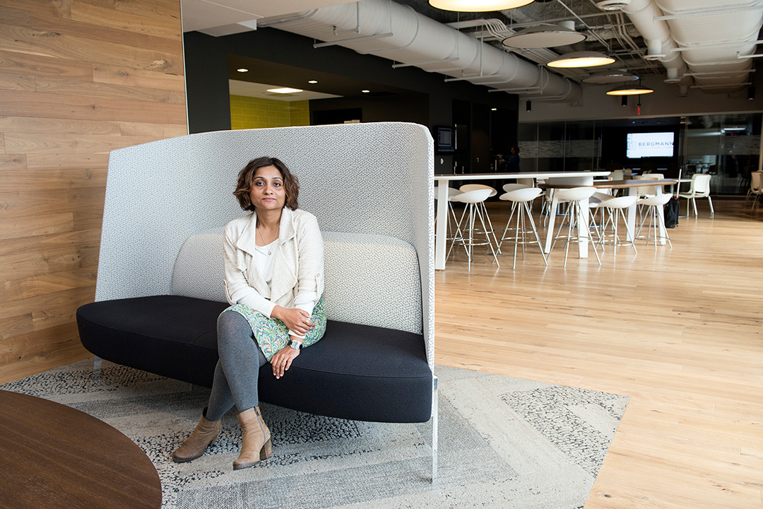 woman in gray tights and white top sits in open-concept lounge area