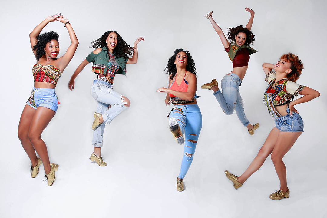 Five women dressed in jeans, colorful clothing and tap shoes jump in the air.