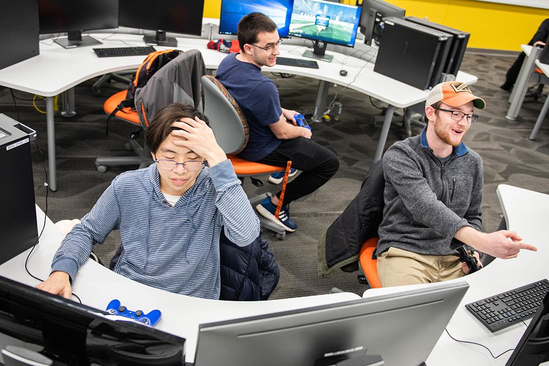 three students sit at computers at half-circle tables