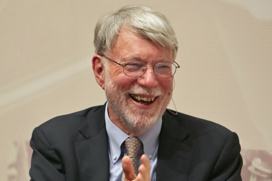 Smiling man with glasses and beard, wearing a suit