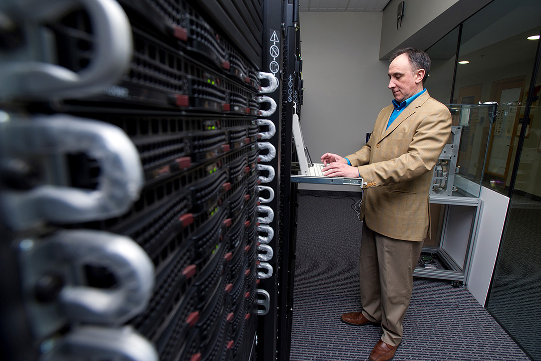 Man in tan suit stands and types on keyboard of supercomputer