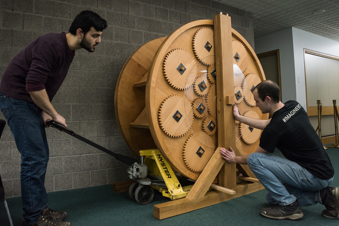 Two students set large wooden wheel with medium and small-sized gears on floor