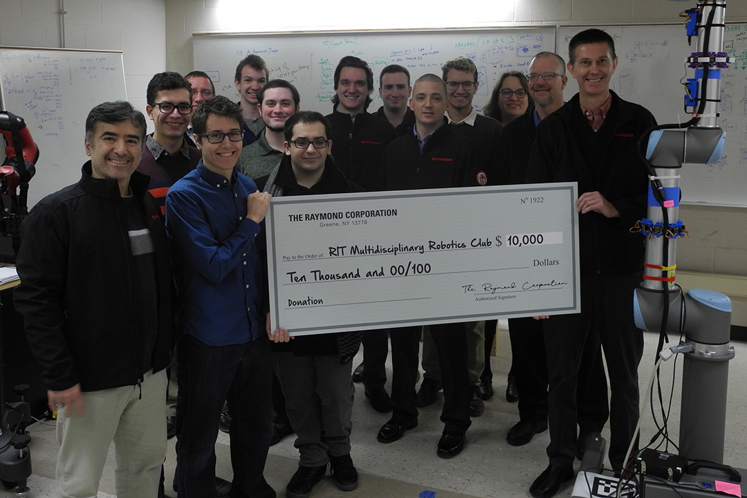 Group of students and professors stands holding giant check for $10,000 from the Raymond Corporation