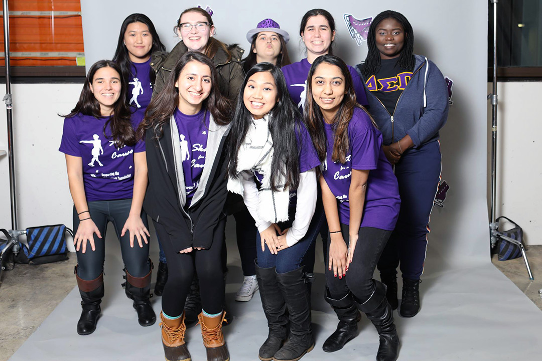 Group of nine female students wearing purple T-shirts stands together in front of white backdrop