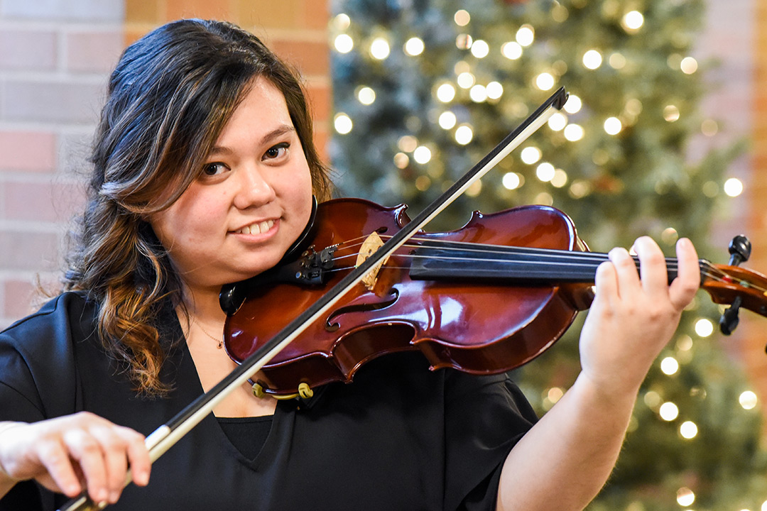 student poses with violin