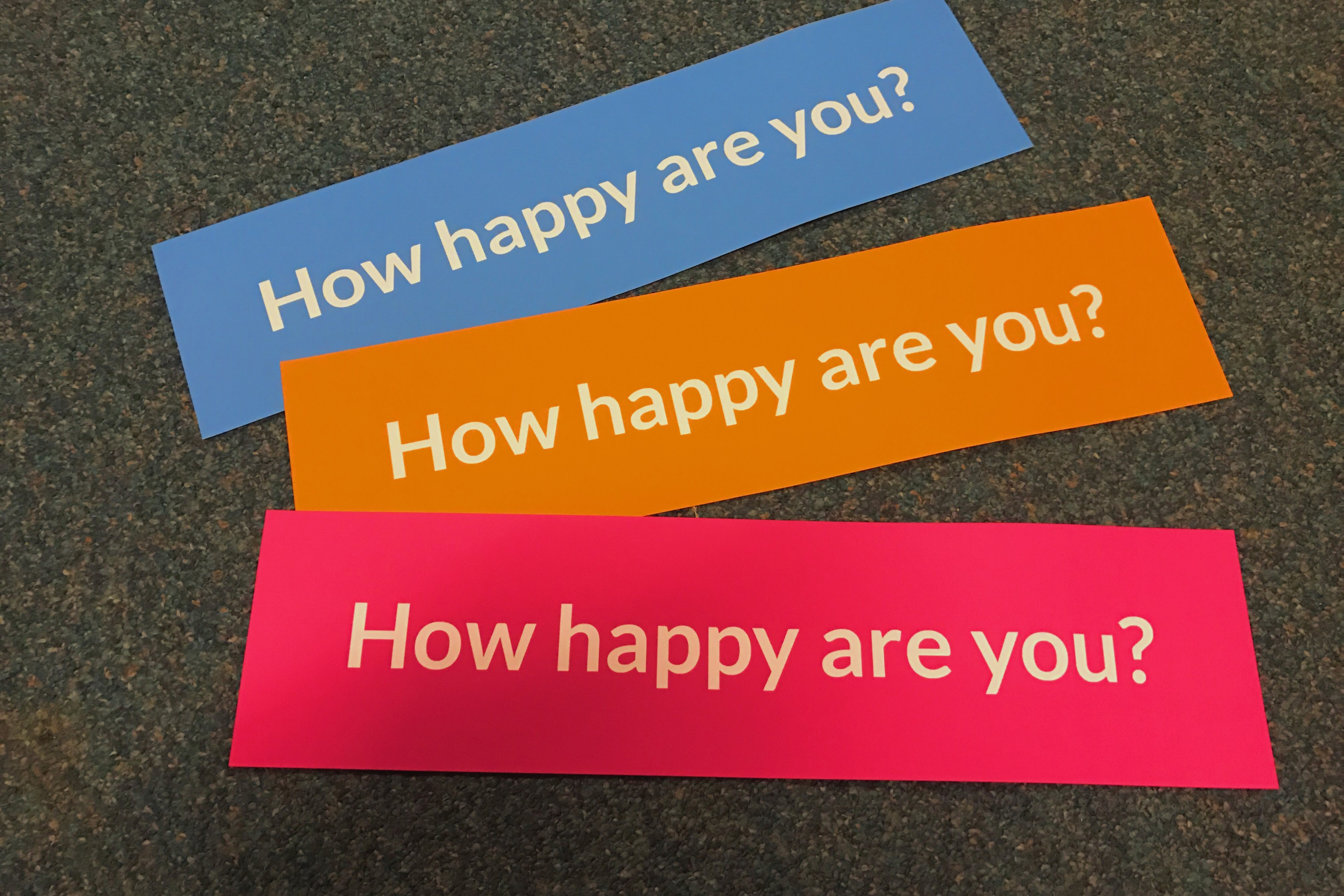 """3 signs of different colors with the text """"How happy are you?"""""""