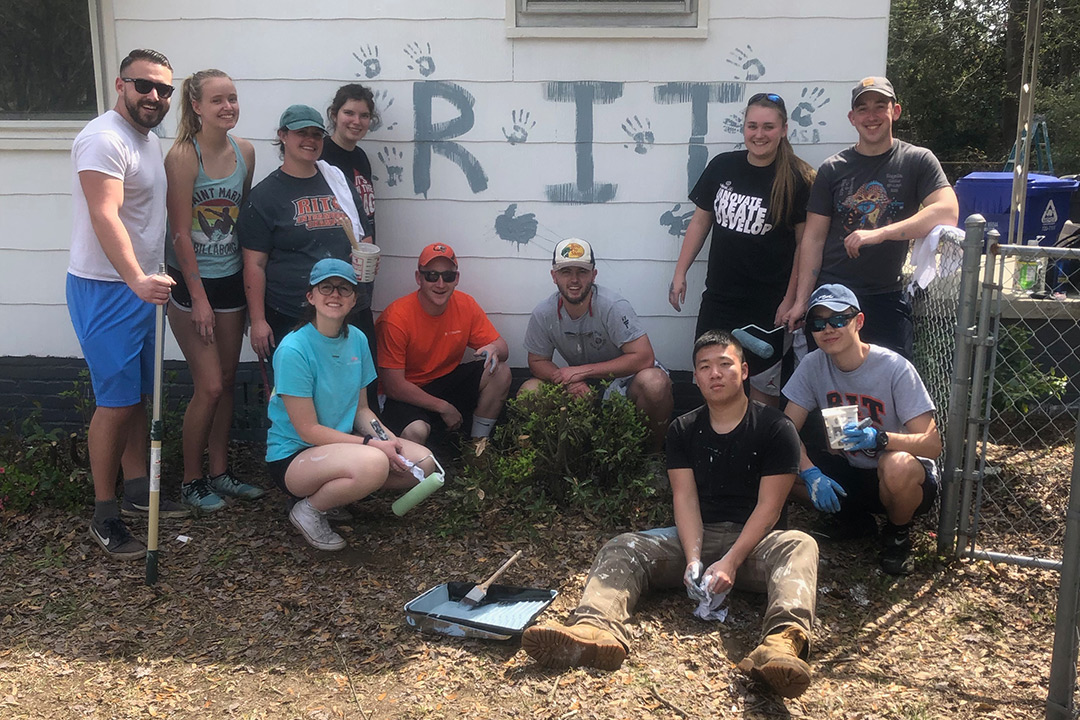 Group of students poses around outside of a house they are painting, with the letters RIT and their handprints painted on the house exterior.