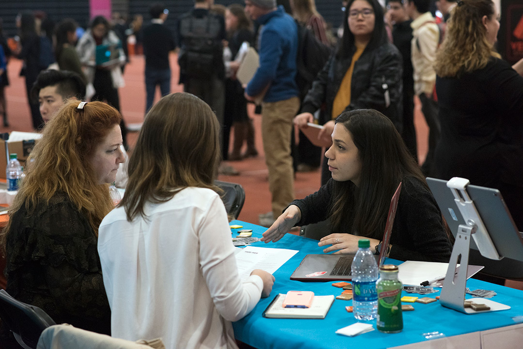 Student sits at table talking to company reps in career-fair setting