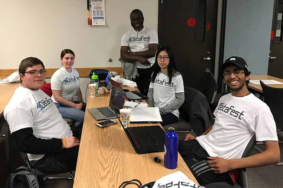 Group of five students and professor sit around table wearing T-shirts that read: DataFest