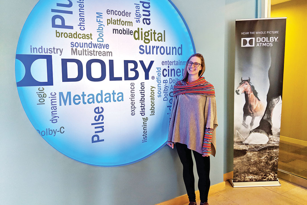Woman standing next to Dolby sign