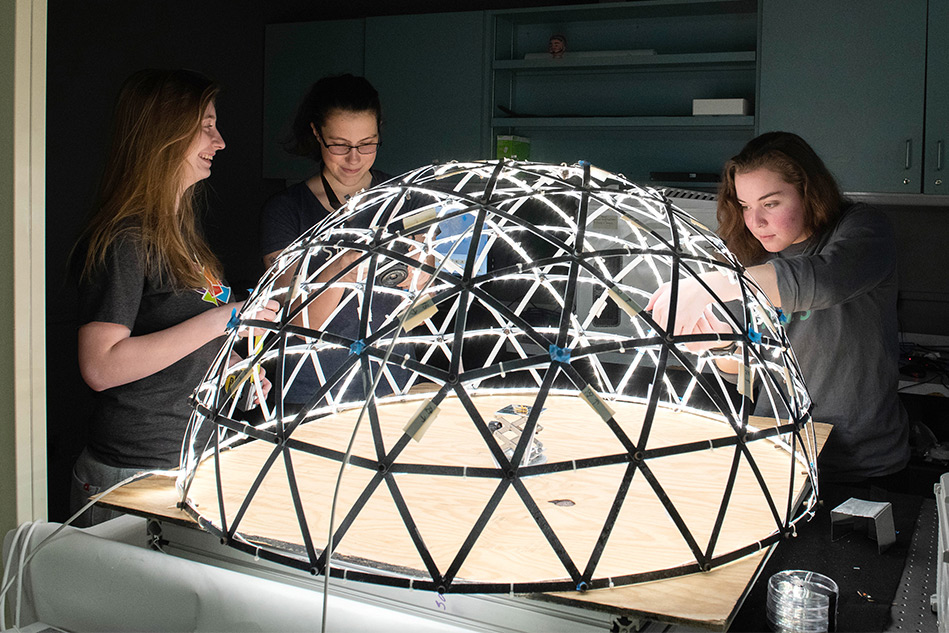 Three students stand around lighted spherical structure on a table.