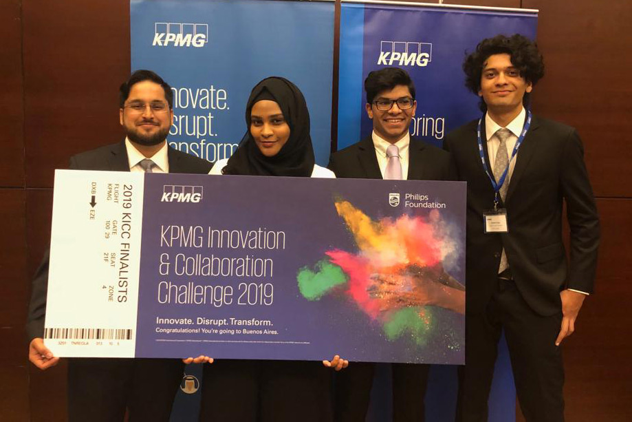 Four RIT Dubai students stand holding giant check