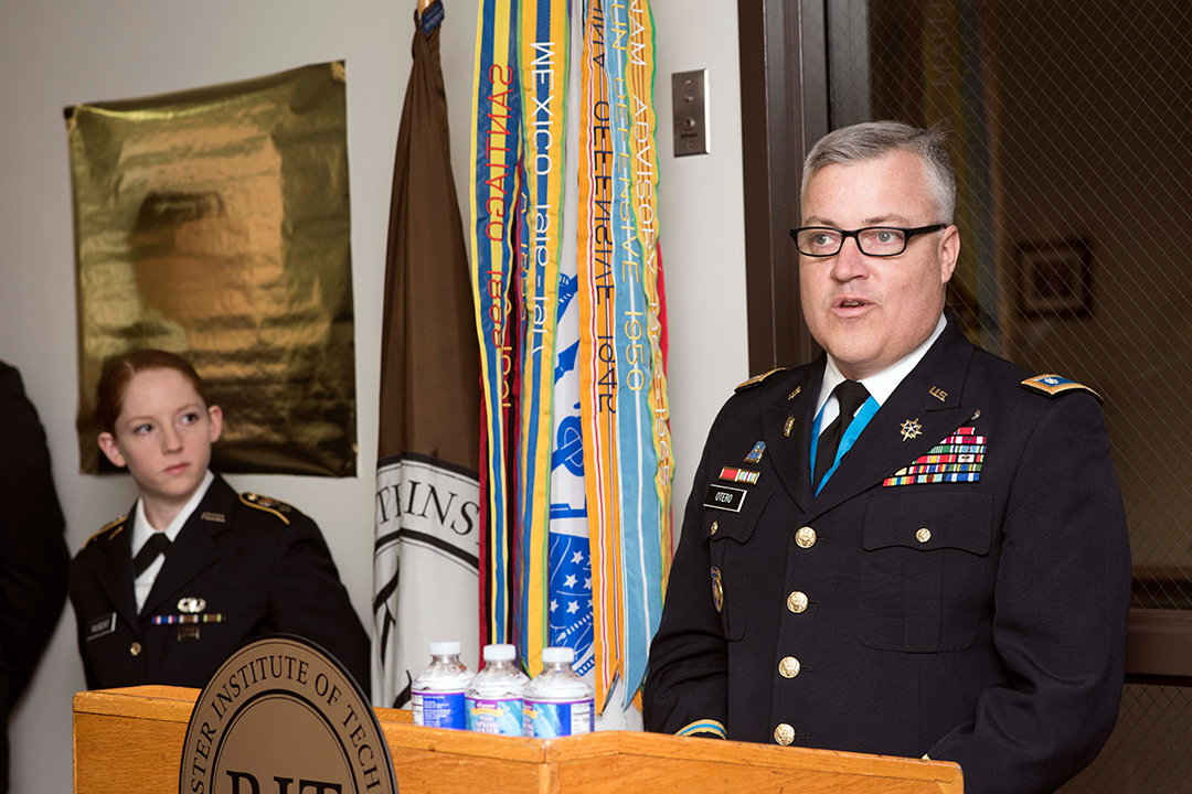 Man in U.S. Army Class A uniform speaks at podium
