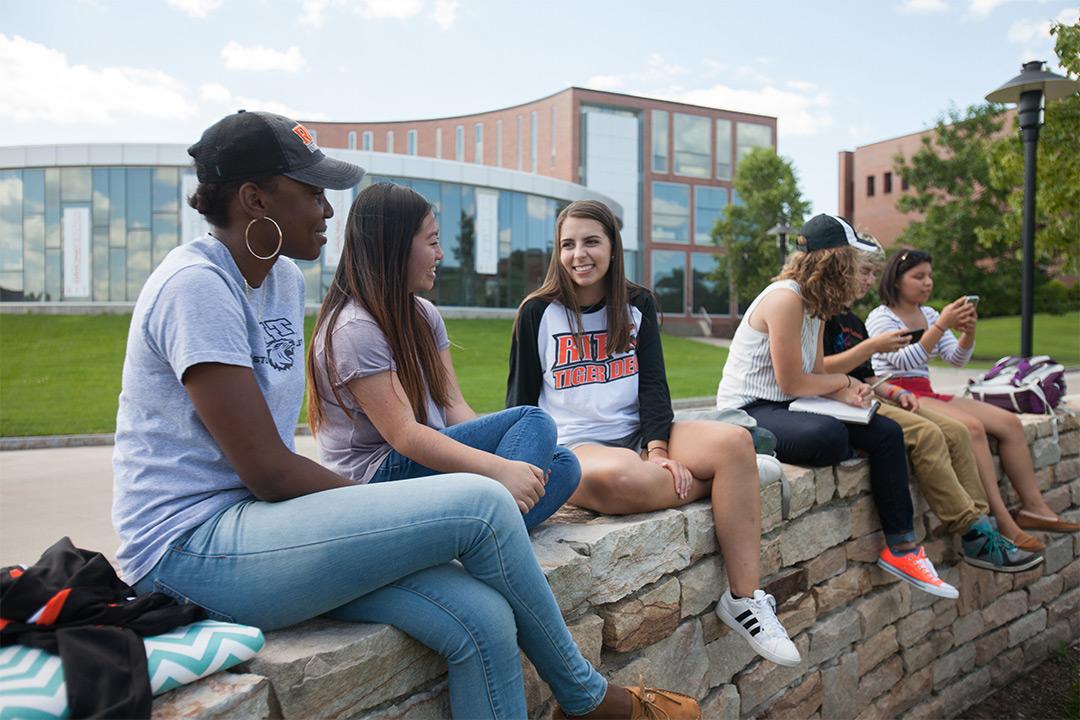 Six students sit on rock wall.