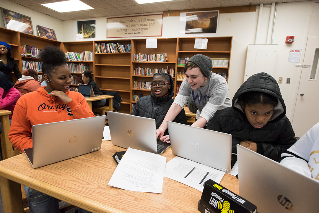 Three high school students and one RIT student sit around table working on laptops