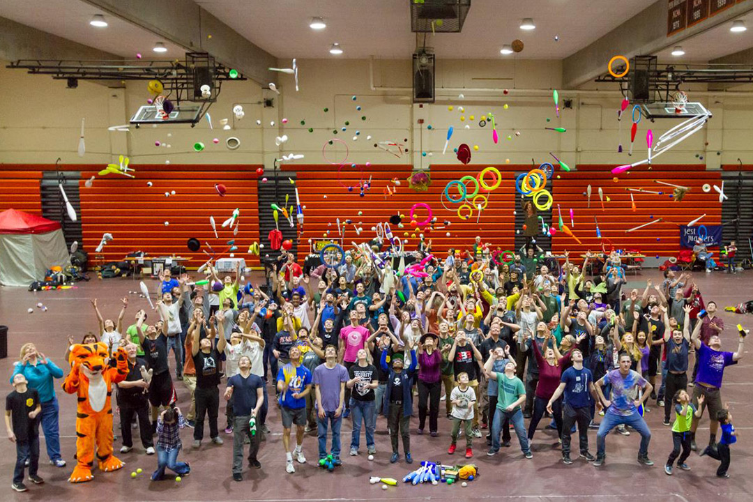 Large group of people throws juggling pins, hoops and balls into the air.