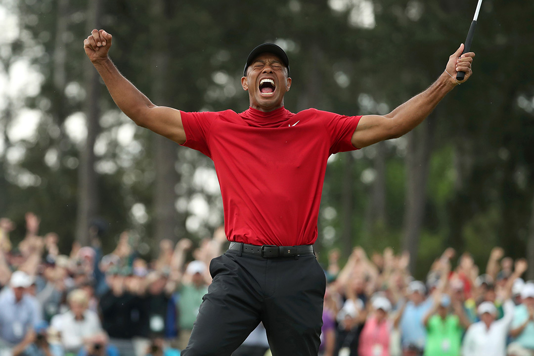 Tiger Woods raises his arms in victory.
