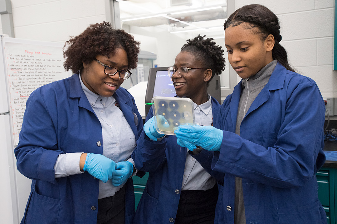 Three high school students wearing blue lab coats examine petri dish.