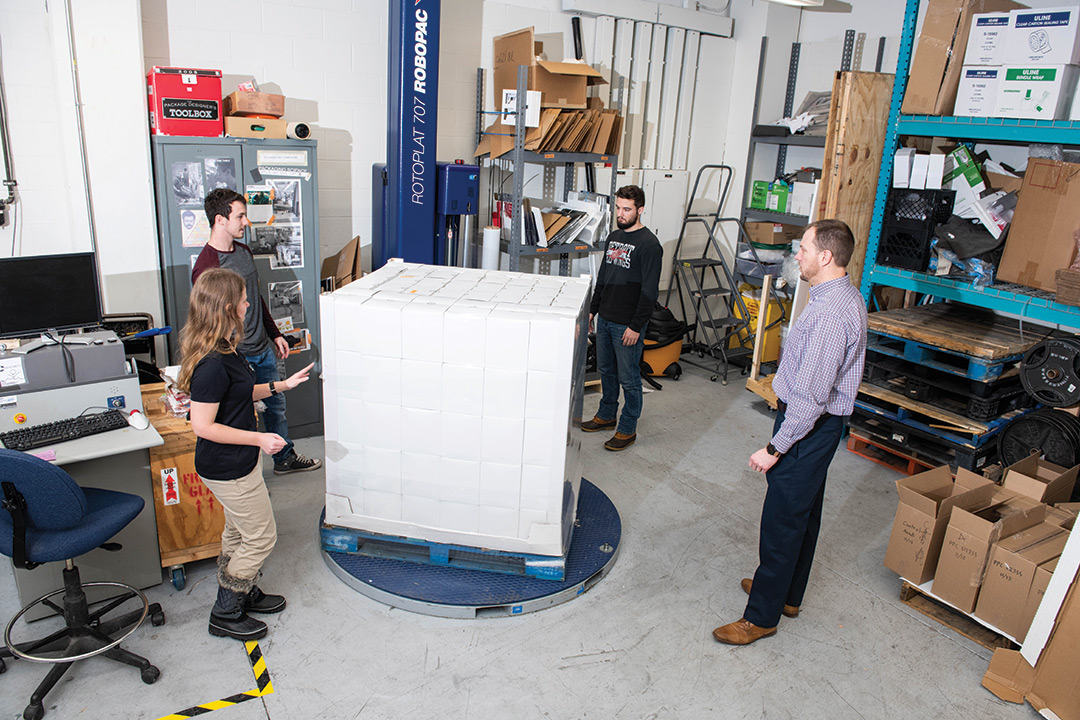 Students and professor stand around pallet with boxes.