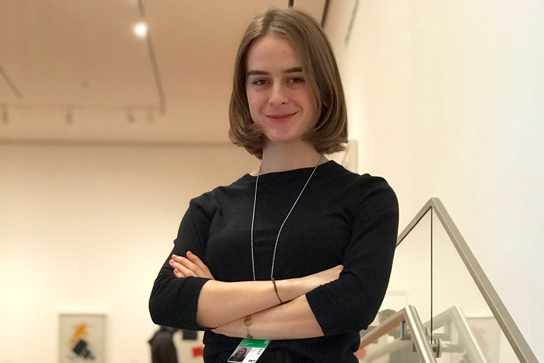 Student stands on stairwell at art museum.