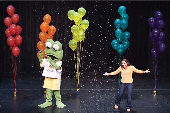 Woman performs on stage with large frog mascot.