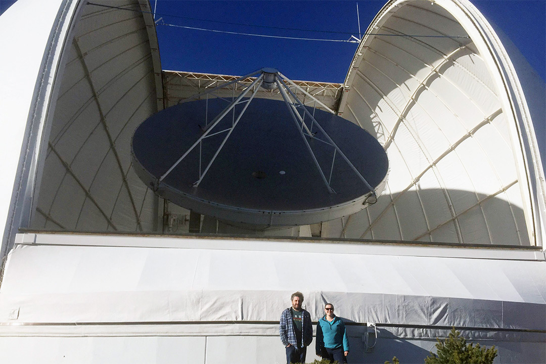 Researchers stand in front of gigantic observatory.